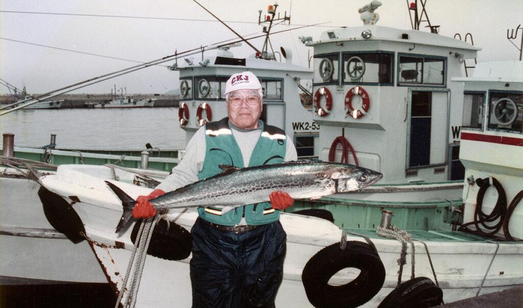 船の前で大きな魚を持って立つ男性